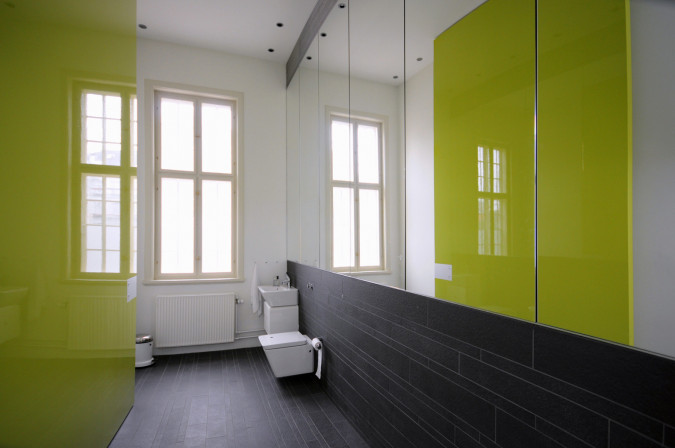 Using the toilets is an experience with the oversized doors painted in remarkable colors.
